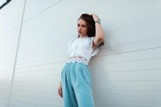 Mulher jovem urbana elegante com roupas de verão elegantes fica perto de um edifício branco moderno na cidade. linda garota morena europeia ao ar livre. estilo de verão na moda da juventude.