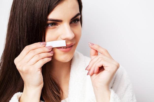 Mulher jovem usa listra branca para remover pelos na região do rosto