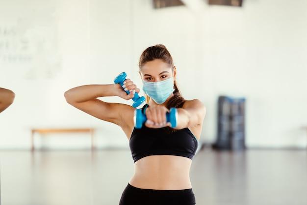 Mulher jovem usa máscara e faz exercícios dentro de casa com halteres