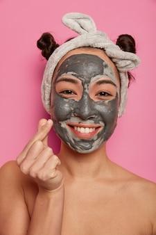 Mulher jovem usa máscara facial natural de argila para tratamentos de pele após o banho