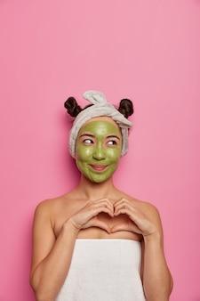 Mulher jovem usa máscara facial natural para tratamentos de pele após tomar banho