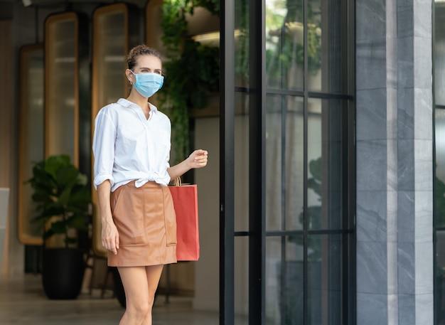 Mulher jovem usa máscara médica protetora carregando sacolas de compras e sai do shopping center