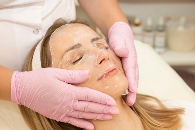 Mulher jovem usa uma máscara de hidrogel no rosto. procedimento no cosmetologista. relaxar