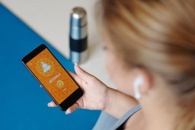 Mulher jovem usando aplicativo móvel ao praticar ioga em casa