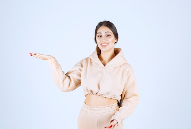 Mulher jovem usando as mãos abertas para apresentar e falar sobre algo
