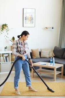 Mulher jovem usando aspirador de pó para passar aspirador de pó no carpete da sala de estar
