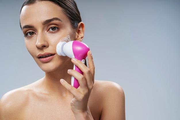 Mulher jovem usando bruch eletrônico para o rosto