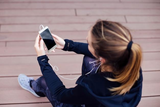 Mulher jovem, usando, cellphone, e, sittinng, ligado, escadas