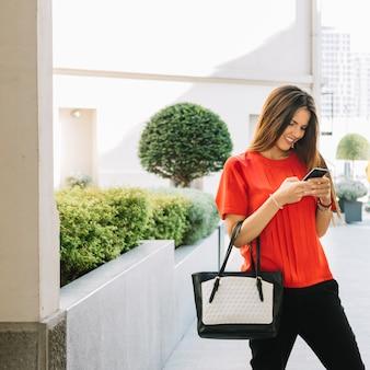 Mulher jovem, usando, cellphone, em, ao ar livre