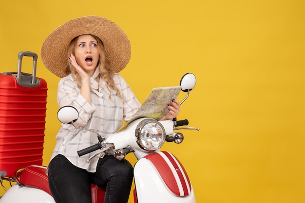 Mulher jovem usando chapéu e sentada em uma motocicleta segurando um mapa e ouvindo as últimas fofocas em amarelo