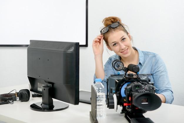 Mulher jovem, usando computador, para, vídeo, editar
