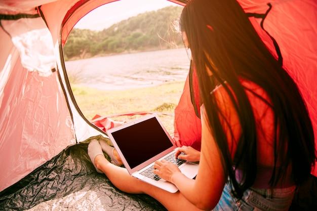 Mulher jovem, usando computador portátil, em, barraca