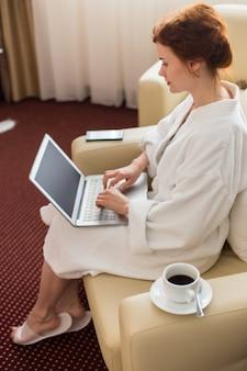 Mulher jovem, usando computador portátil, em, hotel