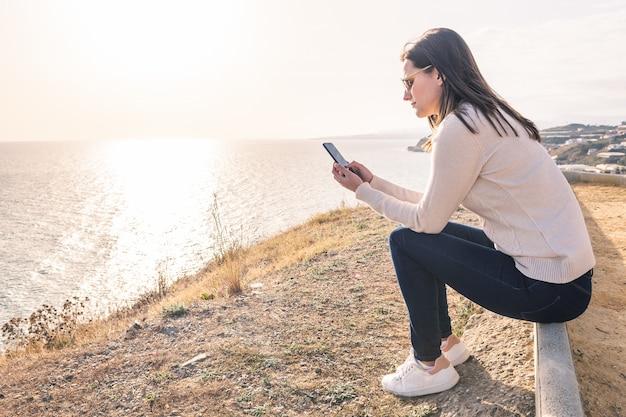Mulher jovem, usando, dela, telefone móvel, frente, a, mar, em, primavera