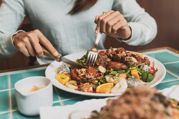 Mulher jovem, usando, faca garfo, para, cortar, carne, em, restaurante