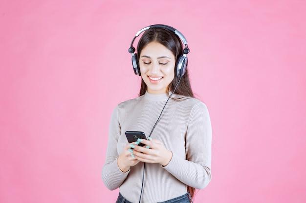 Mulher jovem usando fones de ouvido e configurando música em seu smartphone