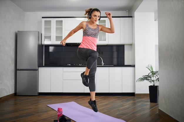 Mulher jovem usando fones de ouvido pulando em casa