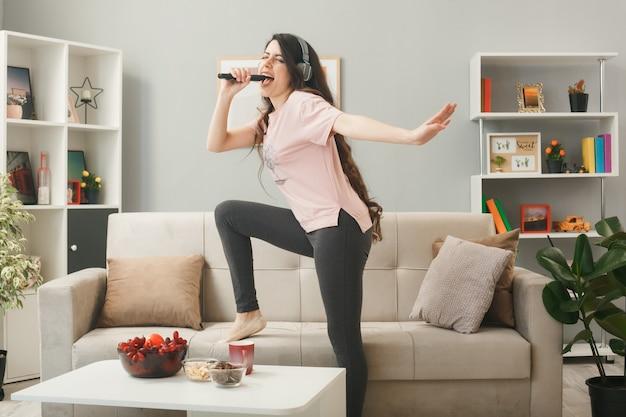 Mulher jovem usando fones de ouvido segurando o microfone canta em pé no sofá atrás da mesa de centro na sala de estar