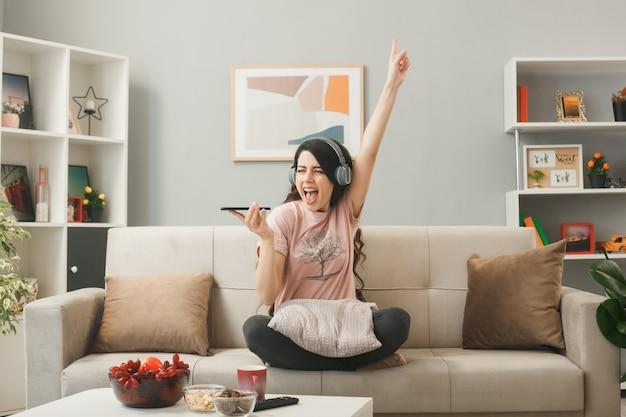 Mulher jovem usando fones de ouvido segurando pontos de telefone em cima, sentada no sofá atrás da mesa de centro na sala de estar