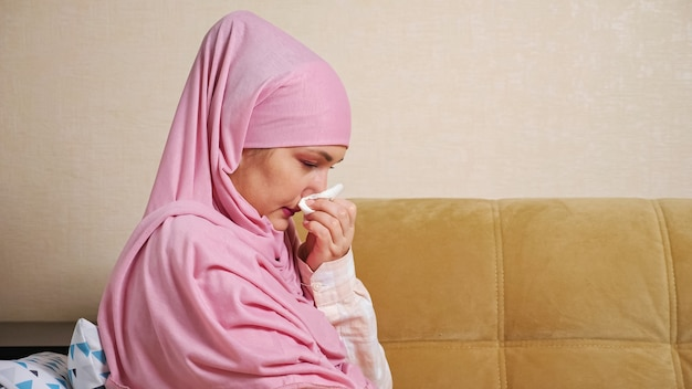 Mulher jovem usando hijab espirra e sofre de corrimento nasal no sofá