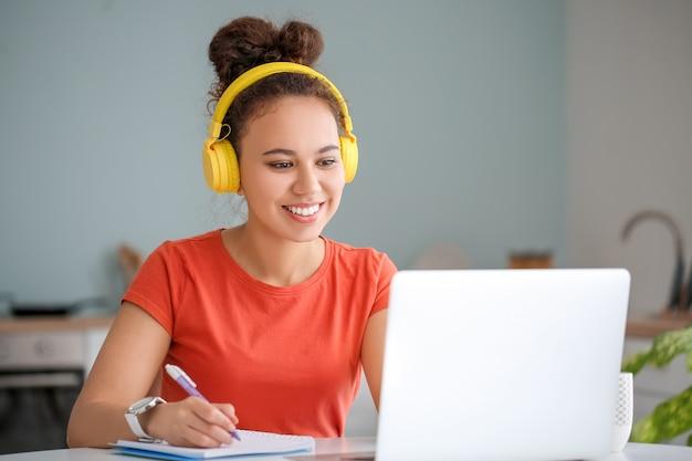 Mulher jovem usando laptop para aprendizado on-line em casa