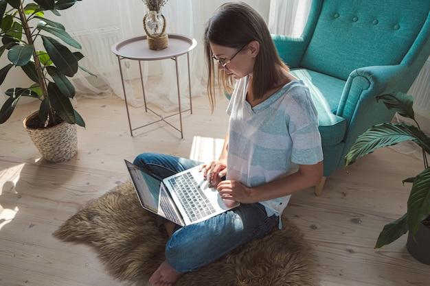 Mulher jovem usando laptop para trabalhar, sentada no chão em casa, horário flexível e trabalho remoto