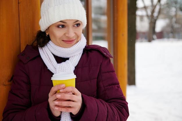 Mulher jovem usando lenço branco e chapéu de lã branco em pé com uma bebida quente para ir em um parque de inverno nevado.