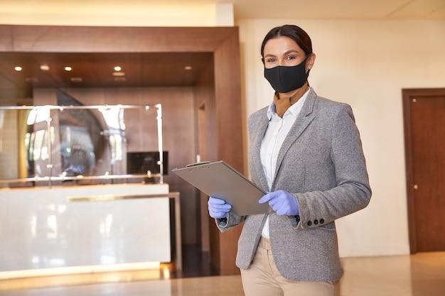 Mulher jovem usando luvas de borracha e uma máscara de tecido enquanto está em um saguão de hotel com uma prancheta