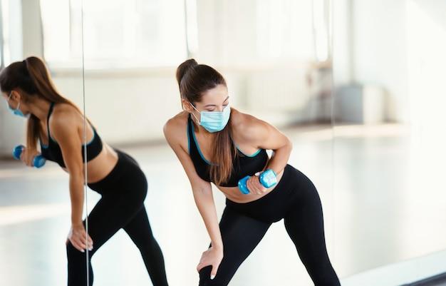 Mulher jovem usando máscara e fazendo exercícios com halteres