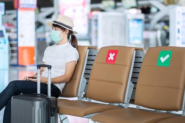Mulher jovem usando máscara facial e sentada na cadeira no aeroporto, infecção por doença de coronavirus (covid-19) de proteção, viajante de mulher asiática. novo normal, bolha de viagens e distanciamento social