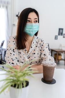 Mulher jovem usando máscara facial para proteção contra o coronavírus (covid-19) e bebendo leite com chocolate em um café