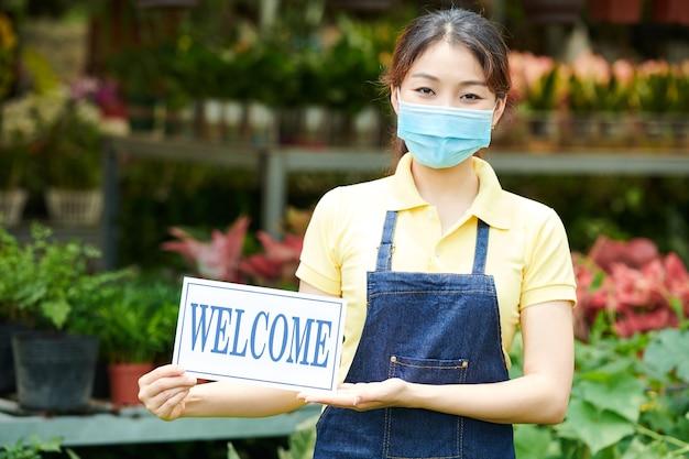 Mulher jovem usando máscara médica ao convidar clientes para um centro de jardinagem ou viveiro de plantas