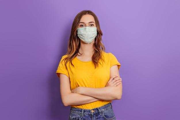 Mulher jovem usando máscara médica em pé com os braços cruzados, isolado em um fundo lilás
