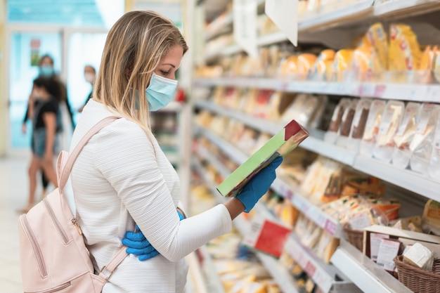 Mulher jovem usando máscara protetora em supermercado durante surto de coronavírus