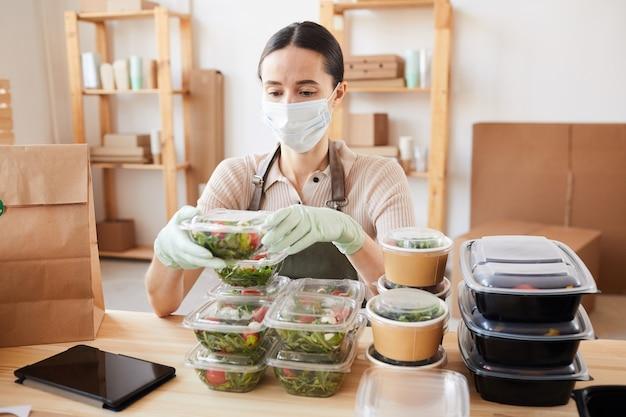 Mulher jovem usando máscara protetora, embalando alimentos saudáveis em caixas, ela está sentada à mesa e trabalhando no escritório