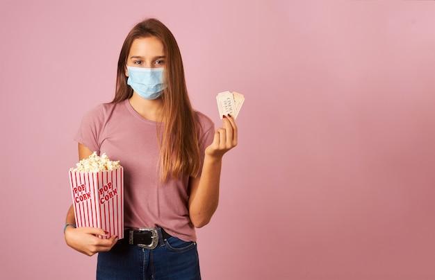 Mulher jovem usando máscara segurando pipoca e ingressos de cinema
