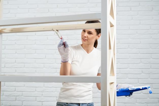 Mulher jovem usando o pincel e a cor branca para a prateleira de pintura