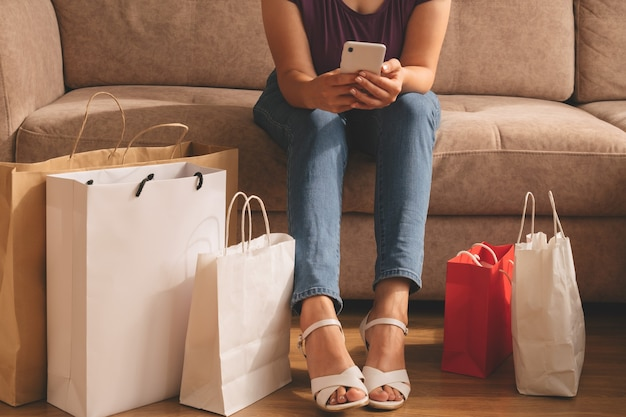 Mulher jovem usando o telefone e sentada em um sofá com muitas sacolas de compras no chão