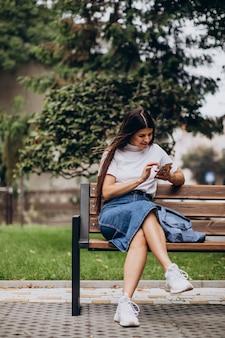 Mulher jovem usando o telefone e sentada no banco do parque