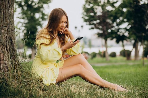 Mulher jovem usando o telefone e sentada sob uma árvore no parque