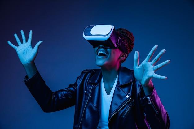 Mulher jovem usando óculos de realidade virtual em luz de néon