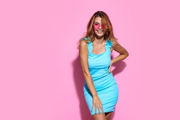Mulher jovem usando óculos escuros e vestido olhando diretamente para a câmera enquanto posa em um estúdio rosa.