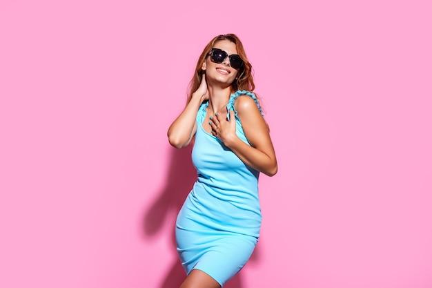 Mulher jovem usando óculos escuros e vestido posando no fundo rosa do estúdio