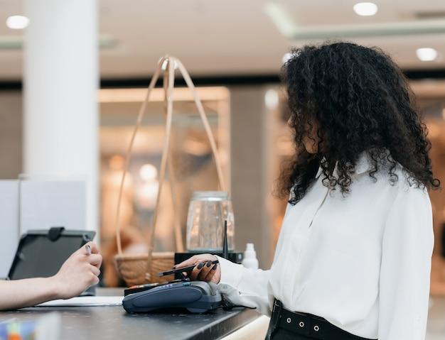 Mulher jovem usando seu smartphone para pagamento sem contato em um café