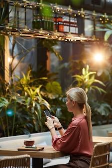 Mulher jovem usando seu telefone celular enquanto está sentada à mesa durante o almoço em um café