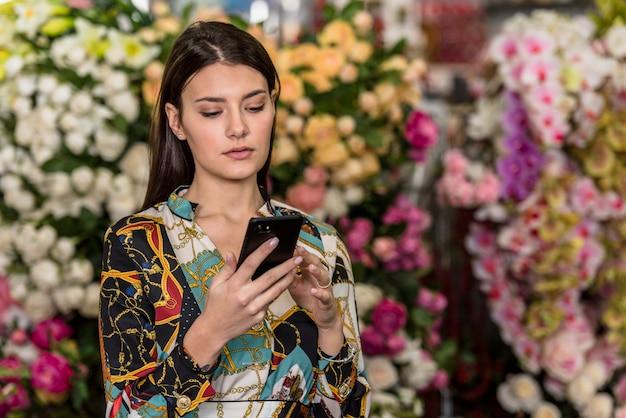 Mulher jovem, usando, smartphone, em, casa verde