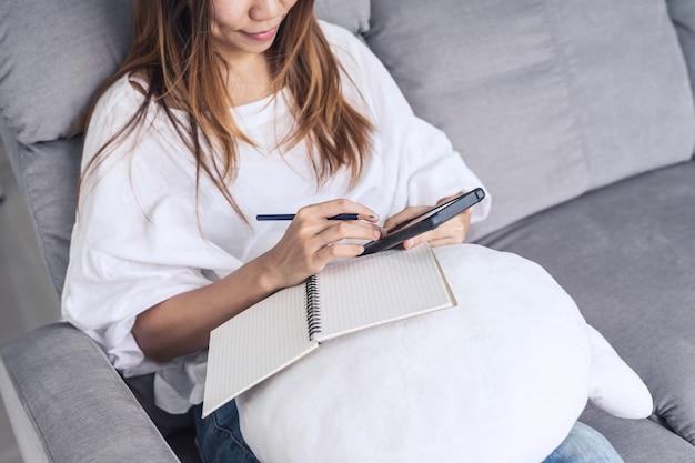 Mulher jovem, usando, smartphone, em, cozy, lar, ligado, sofá, em, sala de estar