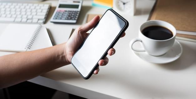 Mulher jovem usando smartphone (tela de toque) para trabalhar com a mesa de trabalho