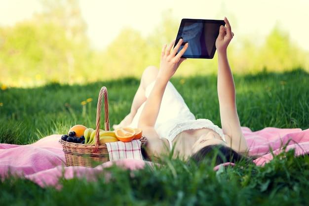 Mulher jovem usando tablet digital no prado