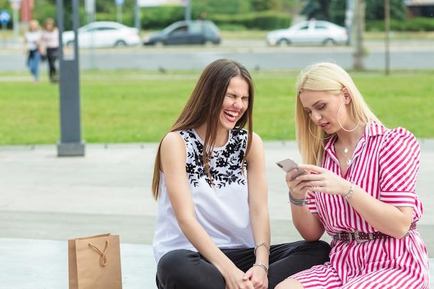 Mulher jovem, usando, telefone móvel, com, dela, amigos, rir, em, jardim